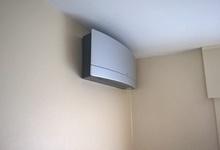 Aircotoestel in een woonkamer. Model Daikin Emura. Foto van toestel in stand 'uit'. (Bruyland Technics).